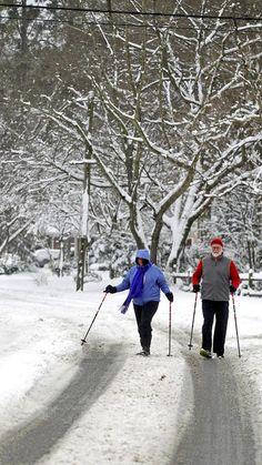 Tama and Jerry Dingus use trekking poles to navigate Shoe Lane in Newport News Thursday morning. (Photo by Jonathon Gruenke / Daily Press)