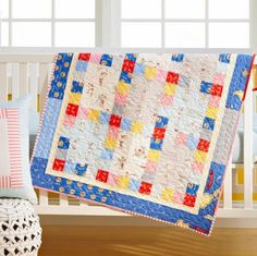 Keep it simple. One bright red print adds a shot of color to the scrappy quilt. Novelty sea prints add a whimsical touch.