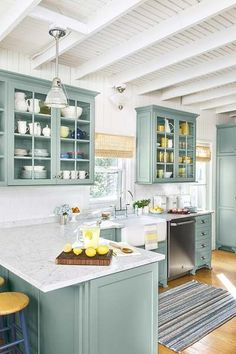 marble countertops set on an l-shaped counter with pale green top-and-bottom cabinets with white exposed beams on the ceiling for the must-have, money-saving kitchen upgrades gallery