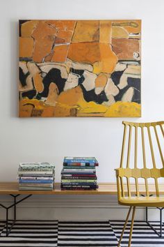 Midcentury Furniture: A bench topped with stacks of books beside a yellow chair.