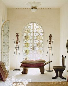 African Bedroom: Liza Bruce's Moroccan Home -     In a guest bedroom, Mauritanian tent pegs flank a West African bed; the carved-wood chair and the buffalo-hide shield are from Ethiopia.
