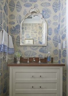 Beach cottage powder room features ivory and blue seashell wallpaper framing silver seashell mirror over ivory washstand with drawers accented with lucite pulls topped with wood top. Coastal Bathrooms, Beach Bathrooms, Half Bathrooms, Silver Wallpaper Bathroom, Seaside Wallpaper, Bold Wallpaper, Home Beach, Bathroom Vanity Designs, Bathroom Vanities