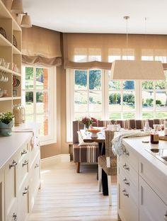 Cocina con banco en el office. Cocina y office con grandes ventanales al exterior