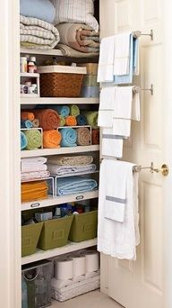 Love this linen closet!  And GEEENIOUS idea to take advantage of inside door... Multiple towel racks to hang towels in sets!