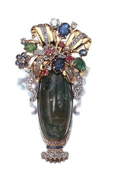 Gold, Platinum, Cabochon Emerald, Gem-Set and Diamond Clip-Brooch  The stylized flower vase with diamond-set handles, fashioned as one oval cabochon emerald, approximately 32.0 x 15.8 mm, the base accented by rose-cut diamonds and French-cut sapphires, topped by a floral design highlighted by 4 carved sapphire and emerald leaves and gem-set and diamond florets, set with 4 old European-cut diamonds, approximately .65 ct., circa 1940.
