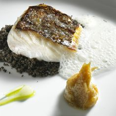 Oven-roasted hake with cep foam, served over torrified black olives. Crispy pastry, deep-fried in sereh oil, on the side.