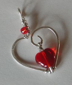 """Heart Pendant hand forged sterling with red Czech glass heart bead and seed bead. I hand formed and hammered this pendent with 18guage sterling wire, the beads are hand wired on with 22 gauge flat sterling wire. It measures 1 1/2""""."""