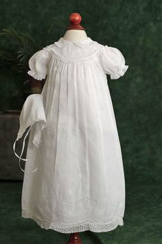 "An adorable 28"" christening gown that has exquisite snowflake and flower  embroidery on the bodice and on the skirt. The Peter Pan collar, sleeves and scalloped hem all are trimmed in lace.  Several deep pleats across the bodice add fullness to the high-waisted gown, a great cut to make little babie..."