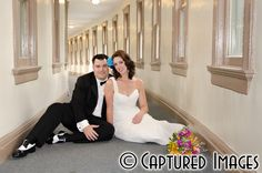 Bride & Groom sitting in hallway for a casual portrait - Blue & Purple Flowers in Bride's hair - Orange, Pink, Yellow Bridal Bouquet
