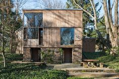 Louis Kahn's Fisher House has a stone base, wood siding, large picture windows, a stone patio, high ceilings and ivy-covered lawn.