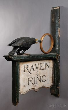 "Carved and Painted ""Raven & Ring"" Tavern Sign, 20th century, fully carved raven and ring motifs, with incised lettering on the shaped double-sided sign, old paint and gilding, on a wood post mounted, 47.5 H. x 32.5 W."