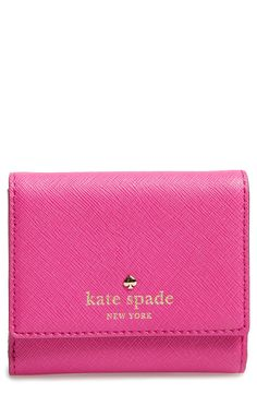 An adorable mini Kate Spade wallet in pink that fits perfectly in a crossbody.