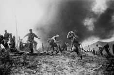 July 15, 1966: US Marines scatter as a CH-46 helicopter burns, background, after it was shot down near the demilitarised zone (DMZ) between North and South Vietnam