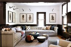 classic living room with cream L shaped sofa, black wainscoting and white walls, black and white feather prints