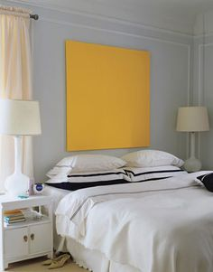 Colorblocked Canvas  Hanging a stretched canvas in a bold hue complements the mod decor and neutral color palette