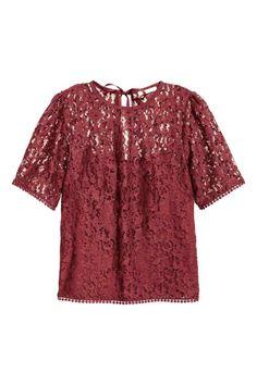 Kanten top: Een kanten top met korte mouwen en een V-vormige split met striklintjes in de nek. Het voorpand is gevoerd met tricot.