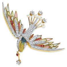 "Masriera Phoenix Brooch. Photo courtesy Cellini Jewelers  ""Art jewel"" of the mythical Phoenix, or Firebird, which is the symbol for rebirth, renewal, and immortality.  Encrusted with round brilliant-cut diamonds, rubies and pearls, and masterfully rendered techniques of enamelwork, in both the transluscent plummage and 'feathered' body; in 18-karat yellow gold. May be worn as brooch or pendant"