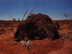 Although the exact location of this photograph is unknown, the structure most likely belongs to the groups found to the west of Alice Springs, such as the Warlpiri and Luritcha. This shelter is predominatly a day-time shade constructed in a dome form by implanting the stems of branches in a circle of holes. It is designed to allow cooking winds to permeate through, but to filter out flies.