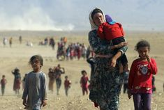 Displaced people from the minority Yazidi sect, fleeing violence from forces loyal to the Islamic State in Sinjar town, walk towards the Syrian border on the outskirts of Sinjar mountain near the Syrian border town of Elierbeh of Al-Hasakah Governorate, in Iraq, August 11, 2014. REUTERS/Rodi Said