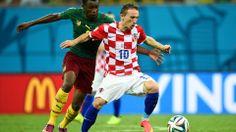 Luka Modric of Croatia holds off a challenge of Benjamin Moukandjo of Cameroon