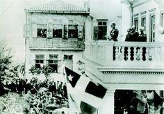"""ΧΑΝΙΑ -9 Δεκεμβρίου 1898 Αφιξη του πρίγκηπα Γεωργίου Γλύξμπουργκ στα Χανιά.  Εκφωνεί διάγγελμα στον λαό της Κρήτης.  Στον εξώστη του κτιρίου κυματίζει η σημαία της Κρητικής Πολιτείας.  Μοναδικές διαφορές από την ελληνική σημαία: το τετράγωνο που φέρει το αστέρι είναι κόκκινο. """"""""- «Κύριοι - απαντά περιφρονητικά - πρέπει να γνωρίζετε πως ήλθα εδώ δια να διοικήσω ως ο Μέγας Πέτρος. Δεν θα δεχθώ του λοιπού αντιρρήσεις εις τας αποφάσεις μου». """""""""""