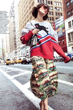 The model embraces a whimsical look in a Gucci sweater, skirt, shoes, bags and shades