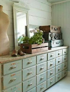 Wall of shabby drawers with library pulls, and nameplates on each drawer. Perfect.