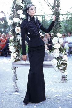 * John Galliano for Dior Belle Epoque inspired Fall/Winter 1997-1998 Model wearing a fitted evening suit consisting of black jacket with two-tone chevron pattern formed by Venetian blind pleats at center front, full-length black skirt, lace cap, and rhinestone pendant earrings. Circa September 1996 © Guy Marineau