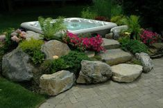 Hot Tub 'In-Garden' Effect: Surrounding this hot tub with rocks and a small garden gives a truly beautiful 'set-in-garden' effect even though it's above ground. Such an installation is much less costly than custom in-ground spas but it's still a beautiful 'backyard escape.'
