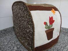 capa p/ máquina de pão, marca Britânia Multi Pane, em tecido 100% algodão, lateral quiltada, forrada e revestida com manta estruturada.  As cores podem variar conforme a disponibilidades dos tecidos.
