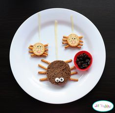 """Sandwich made on pumpernickel bread cut into circle shape. Icing eyes and pretzel stick legs. Mini cracker """"sandwiches"""" with peanut butter. Pretzel stick legs and food safe marker faces. I used mozzarella cheesestrings for the spider's web. Then they have a mini silicone container filled with bugs - aka raisins. Super cute and easy."""