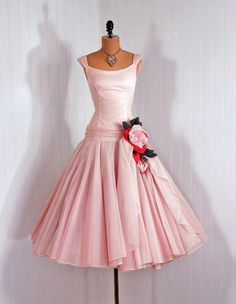 A lovely dropped-waist 1950s dress with a huge rose at the top of the gathered skirt.
