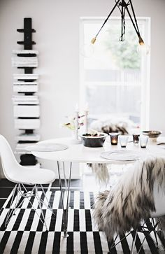 Sheepskin on the back of a dining chair in a monochrome dining room in Sweden.