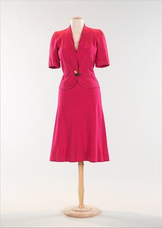 """Suit by Elsa Schiaparelli in her """"shocking  pink"""" color with mermaid button. c. 1938-39  Metropolitan Museum of Art"""
