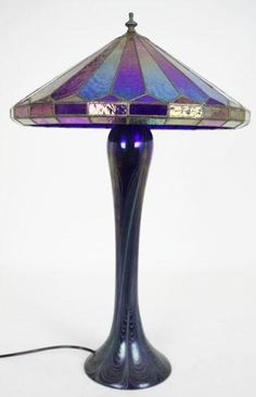An Art Deco Art glass lamp, American 1950. In the style of Tiffany the lamp blue opalescent of baluster form red green, blue and purple panelled shade. 64 cm high.