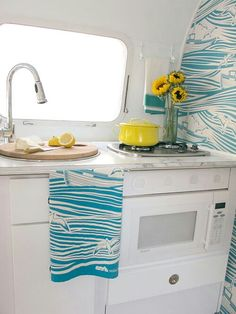 White interior w colour accents and colour squabs, wallpaper behind dinette and/or dbl at other end