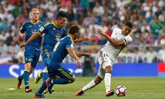 Casemiro shields the ball from a cluster of Celta players.
