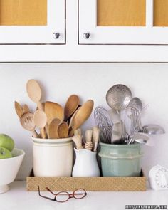 Utensils organized neatly in a low basket, just a splash of subtle color with one utensil crock | Martha Stewart