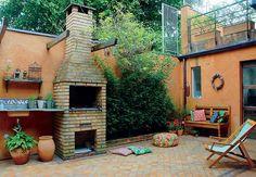Para destacar a parede onde ficam a churrasqueira, o forno de pizza e os armários na área gourmet desta casa, a arquiteta Eliana Marques Lisboa optou por um ladrilho hidráulico geométrico preto e branco.  A coifa foi nivelada com duas prateleiras de madeira