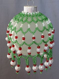 This decorative Christmas Ornament features a handcrafted beaded cover. Perfect for your own tree or that special gift that is unique and affordable. A frosted glass ornament is covered by a netting made of green glass seed beads, red faceted molded beads and molded pearl beads. The