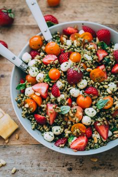 Hearty farro is tossed with homemade pesto, strawberries, tomatoes, and mozzarella cheese to create this beautiful summer grain salad.