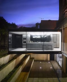 Cross Street, London, by Paul Archer Design. The back wall of the property was removed and the garden excavated to create a two storey elevation of glass, with a bridge structure housing the new kitchen.