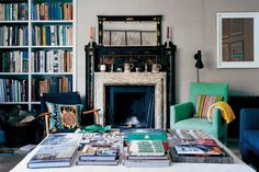 In Ben Pentreath's London living room, mismatched chairs and books atop an ottoman in front of the fireplace. Photo by John Spinks.