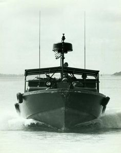 River Patrol Boat (PBR) cuts through the Bassac River, Republic of Vietnam, on the way to an Operation Game Warden patrol, June 1968. Photographed by Lieutenant T.S. Storck, USN
