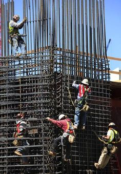 workers are suspended on a wall of steel reinforcement bars rebar as they place