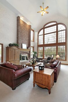 Soaring two story living room contrasts white surroundings with natural textures: hardwood coffee and end tables, full height brick fireplace, and rich burgundy leather sofas stand beneath a massive floor to ceiling window.
