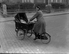 Awesome Vintage Photos of Moms: 1926: A mother gets all the exercise she needs pushing her pram and cycling at the same time and the baby gets a taste for speed at an early age.