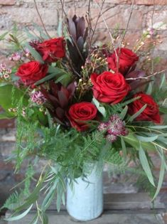 A rustic jug of red Naomi Roses accompanied with delicate pink and  burgundy flowers and seasonal foliage.