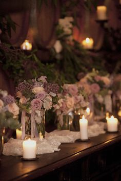 Rustic winery wedding reception centrepiece with purple flowers and candles