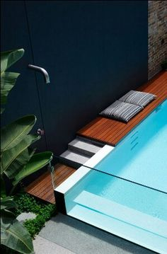 glass ended pool with wood surround boarding and tap style after swim poolside shower